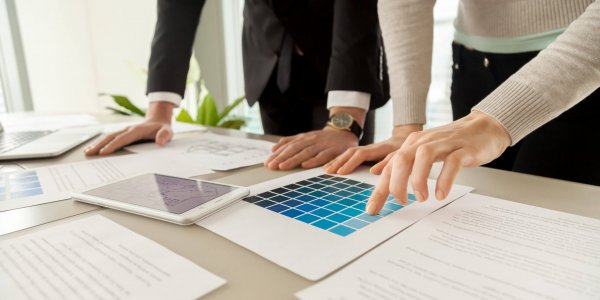 Smiling woman pointing on blue color on pantone swatch on desk while picking house exterior color scheme with architect. Female planning apartments decoration with interior designer. Close up view